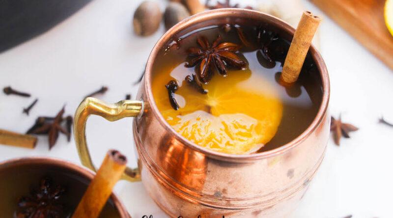 A single mug of cider with a cinnamon stick.