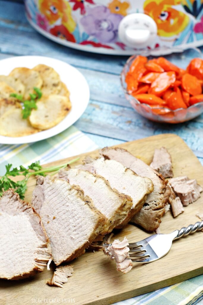 The fully sliced pork roast is laid out on a cutting board with the sides in view in the background.