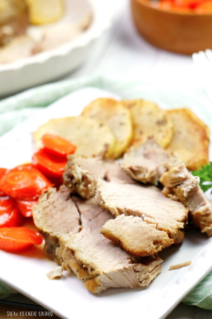 Here we see a close up view of a portion of the crockpot pork roast on a plate with sides ready to be eaten.