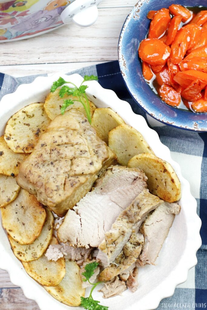 A top down look at the crock pot pork roast on a platter surrounded by potatoes and veggies.