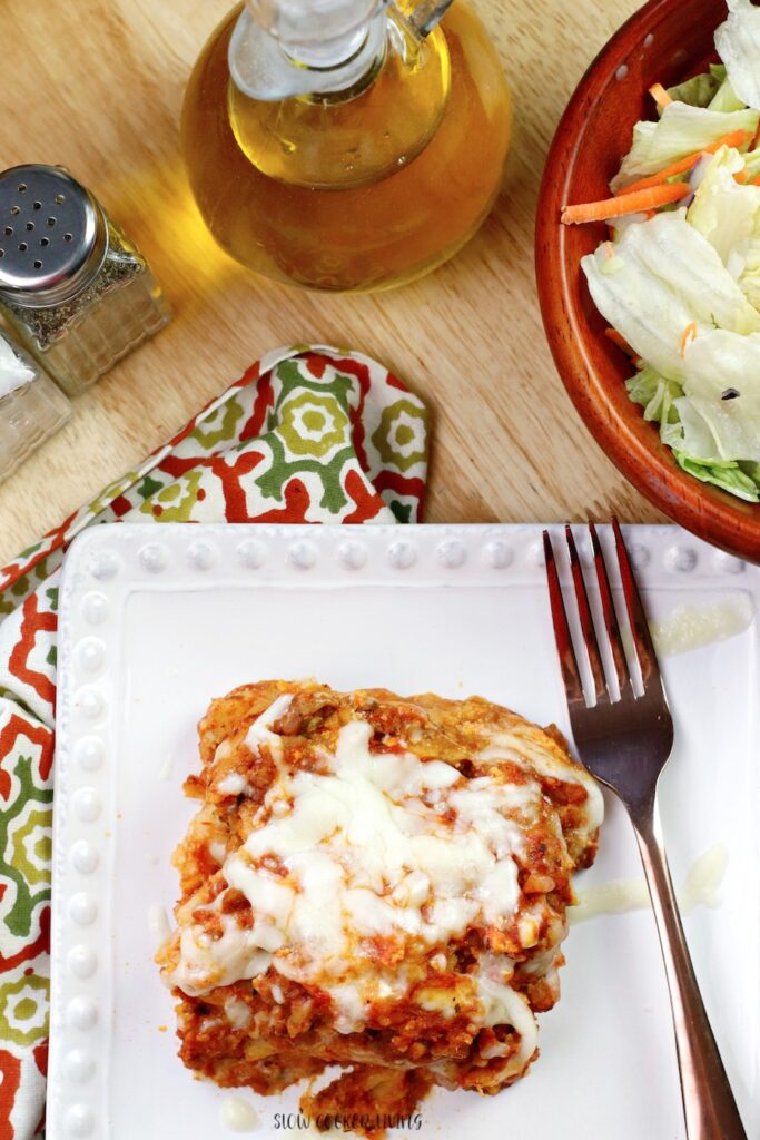 A perfectly cooked lasagna square on a plate ready to be enjoyed.
