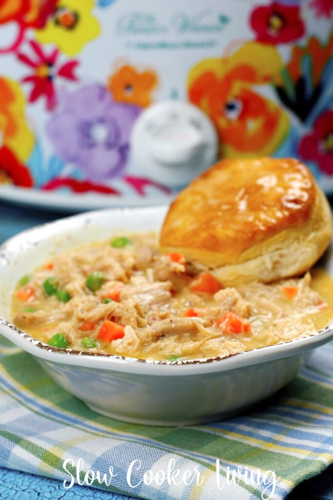here we see a full bowl of chicken pot pie with a biscuit on the side ready to eat.