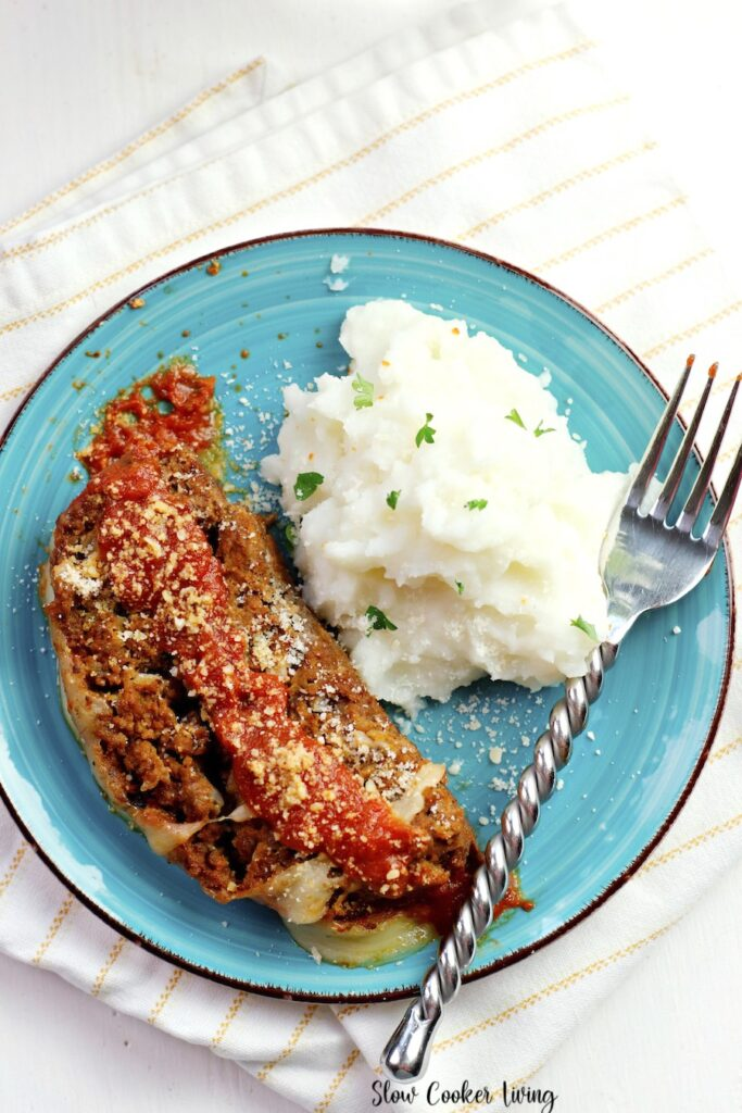 A top down view of a plate with a serving of the Italian crockpot meat loaf recipe and mashed potatoes ready to eat.