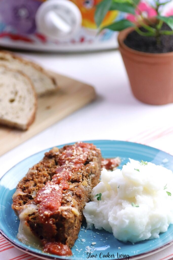 A view of the meatloaf being served with. mashed potatoes on a plate, ready to eat.