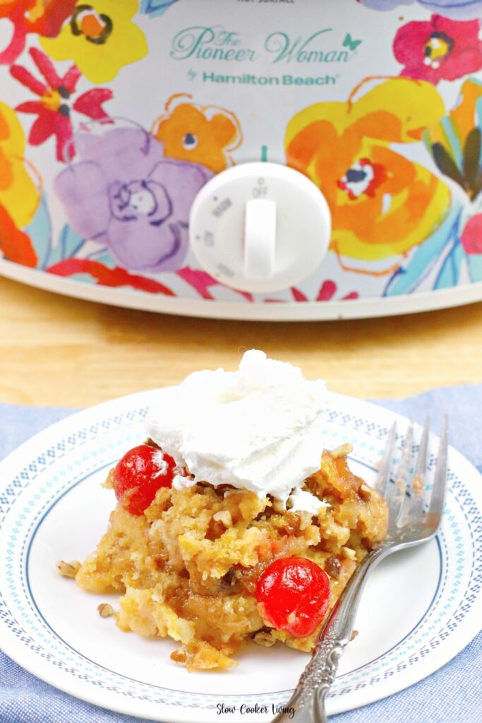 A view of the cake with the crockpot in the background and a fork at the ready to enjoy this delicious dessert recipe.
