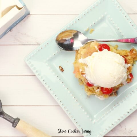 Featured image showing the finished crockpot pineapple upside down cake served with vanilla ice cream on a plate ready to eat.