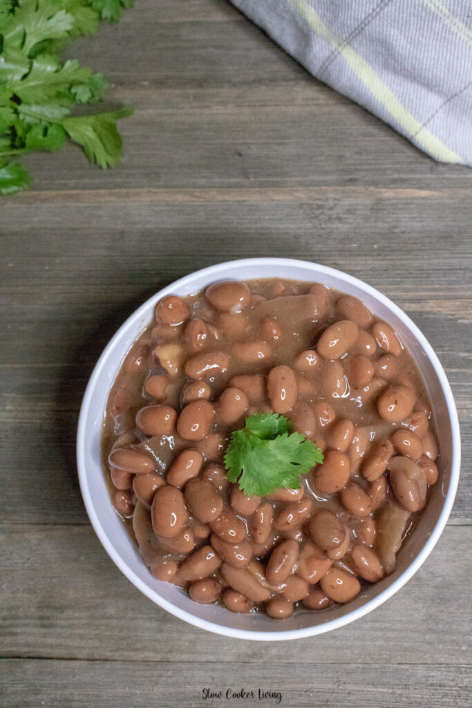 A top down look at a bowl full of finished crockpot pinto beans ready to eat.