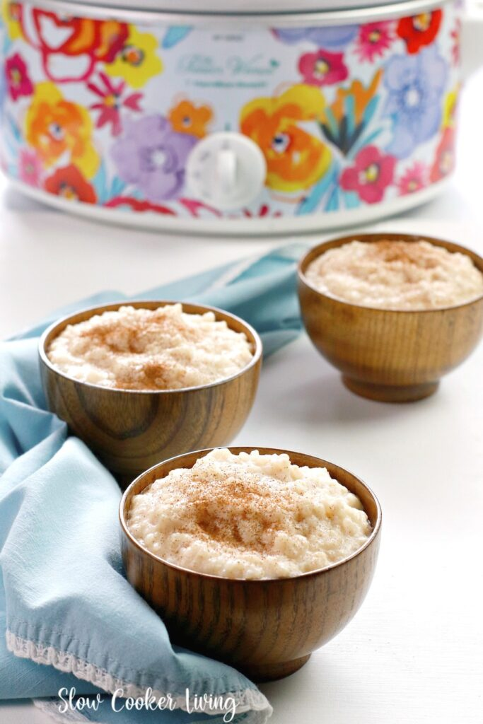 Some wooden bowls full of the finished rice pudding topped with cinnamon ready to eat and share.