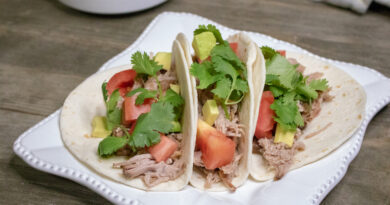 Featured image showing three finished slow cooker tacos ready to eat.