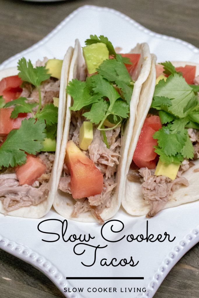 A pin showing the finished slow cooker tacos on a plate with the title at the bottom.