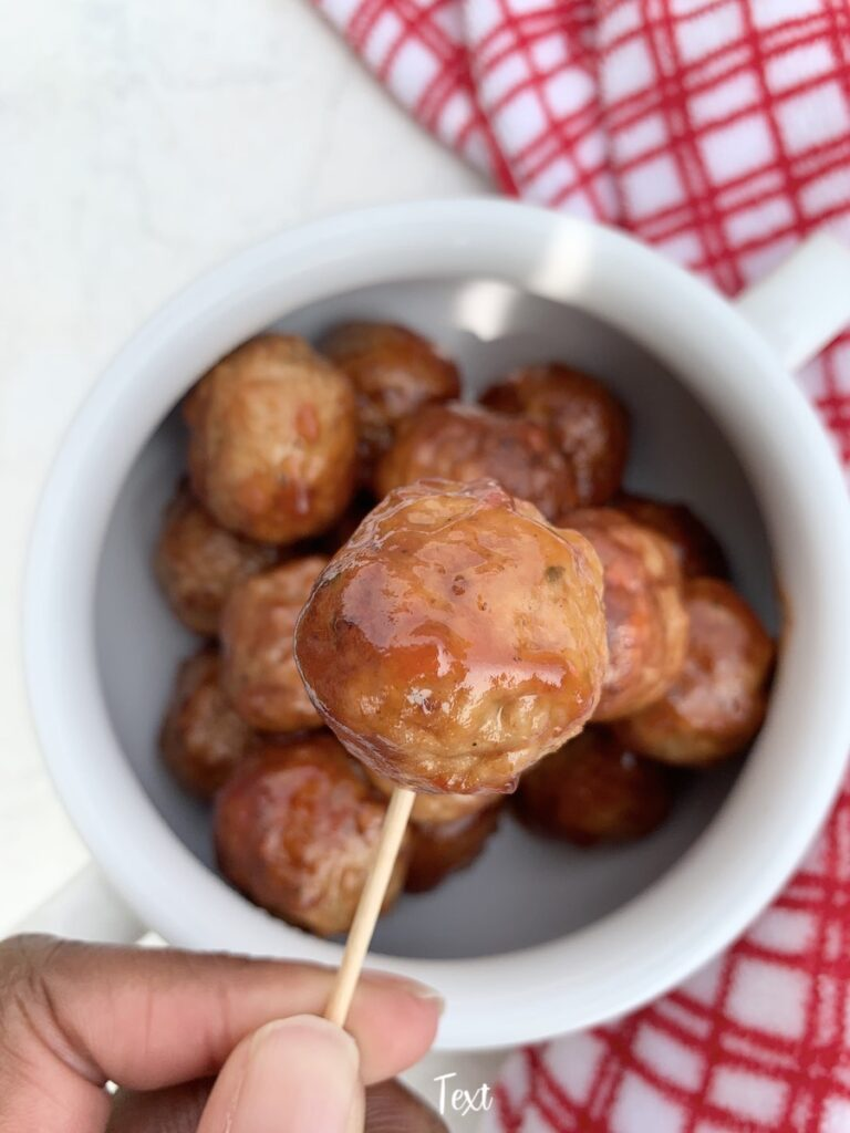 a grape jelly meatball on a toothpick ready to eat.