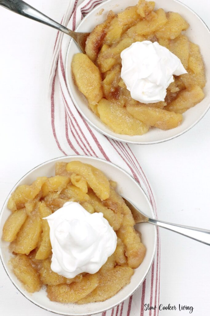 Here we see two servings of the apples topped with whipped cream ready to eat.