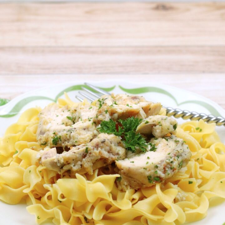 Featured image showing the finished slow cooker garlic parmesan chicken on a bed of noodles.