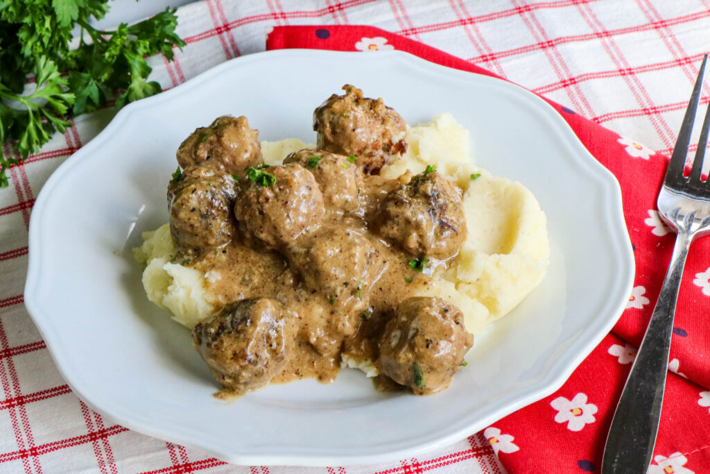 A plate full of Swedish meatballs in the Crockpot ready to eat.