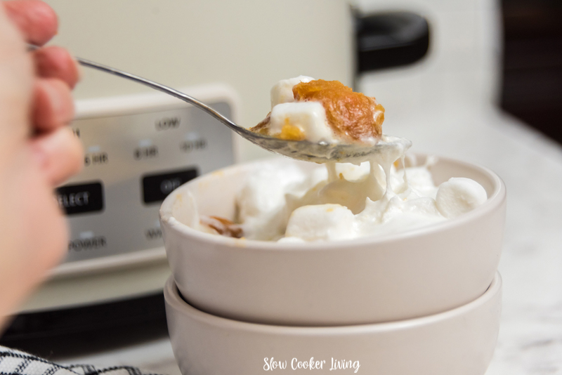 A side look at a spoon full of the finished crockpot sweet potato casserole.