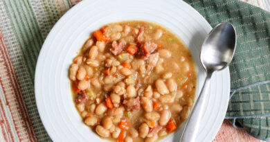 featured image shows a bowl of crockpot bean soup with ham and spoon on the side ready to eat.