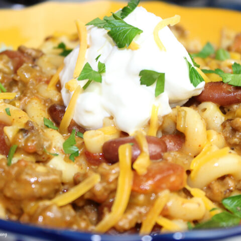 A close up of the finished chili Mac made in the Crockpot topped with whipped cream ready to eat.