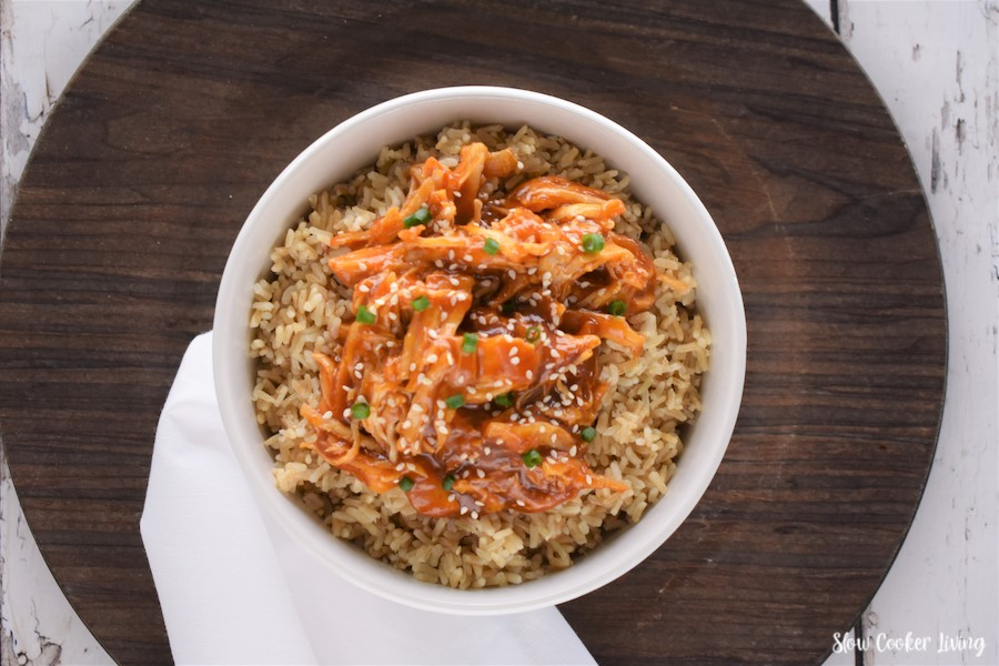 Featured image showing the finished asian crockpot shredded chicken served over rice.