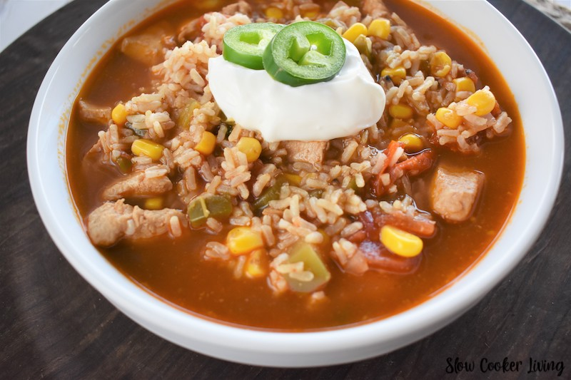 Slow cooker chicken taco soup recipe ready to eat in a bowl with sour cream and jalapeño slices.