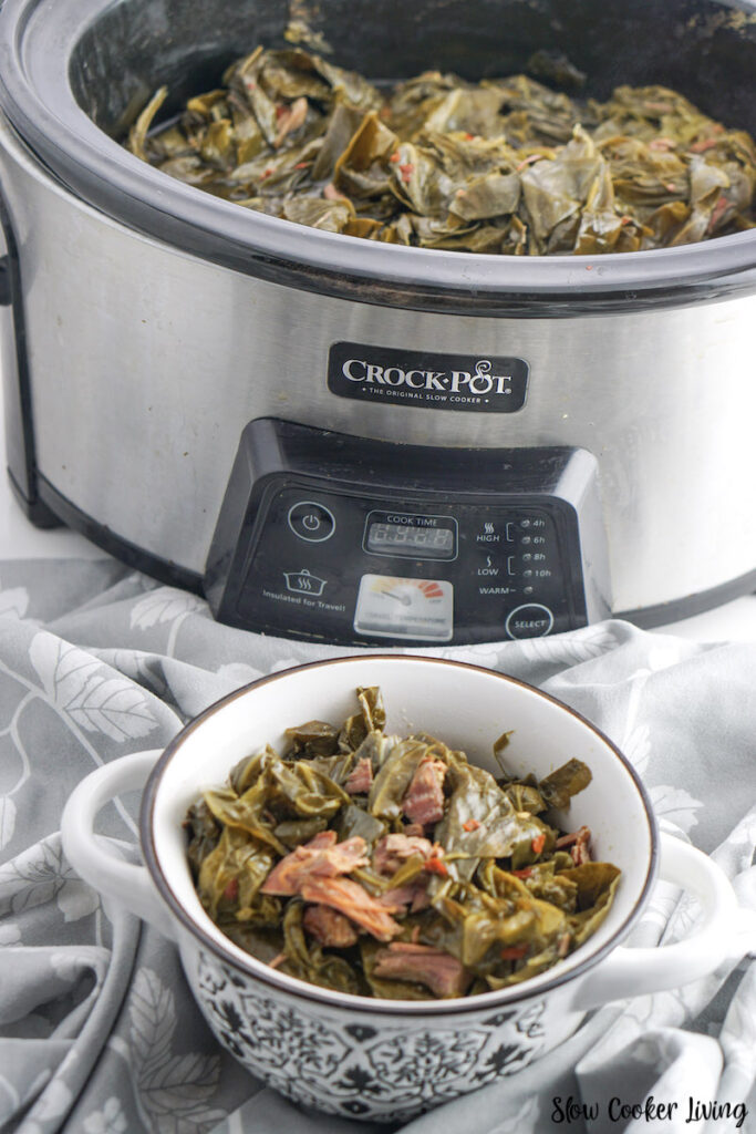 A bowl full of finished greens in from of the Crockpot.
